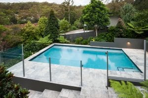 Modern swimming pool with a glass fence on the tile floor covered with a garden with green trees there is a jungle from a distance with some house through it